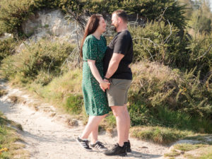 Couple on engagement photo session, standing together on Ham Common, Poole Harbour, Dorset