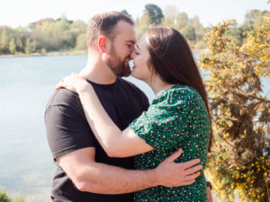 Couple on engagement photo session, about to kiss by the lake on Ham Common, Poole Harbour, Dorset