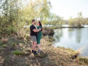 Couple on engagement photo session, holding each other by the lake on Ham Common, Poole Harbour, Dorset