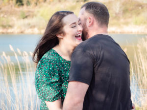 Couple on engagement photo session, sharing a fun memory by the lake on Ham Common, Poole Harbour, Dorset