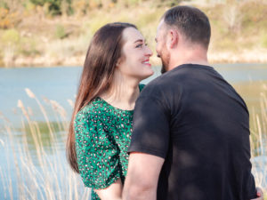 Couple on engagement photo session, smiling at each other by the lake on Ham Common, Poole Harbour, Dorset
