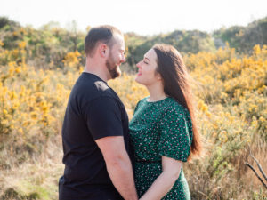 Couple on engagement photo session, gazing lovingly at each other on Ham Common, Poole Harbour, Dorset