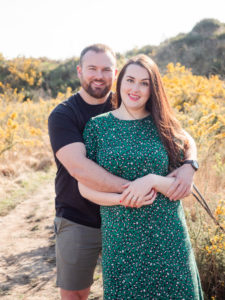 Couple on engagement photo session, posing together on Ham Common, Poole Harbour, Dorset