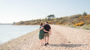Couple on engagement photo session, walking arm-in-arm on Lake Beach, Poole Harbour, Dorset