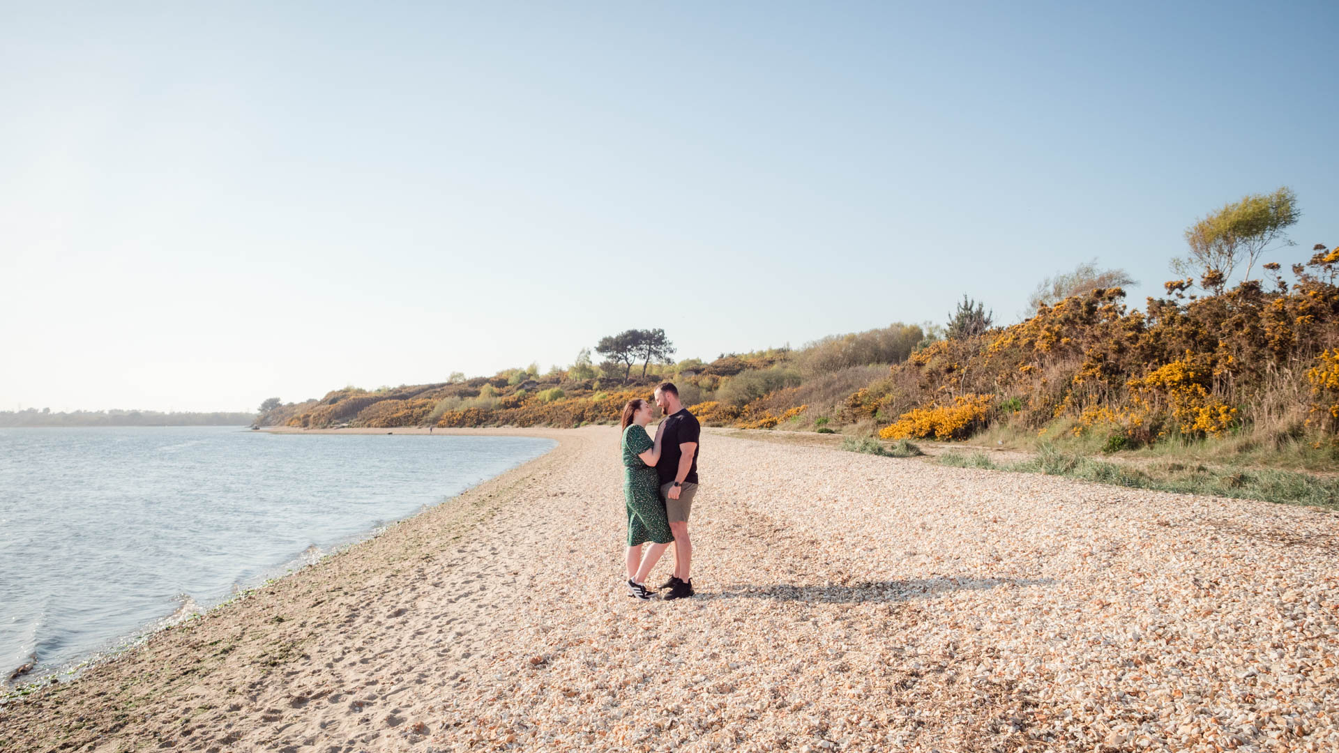 Couple on engagement photo session, standing on Lake Beach, Poole Harbour, Dorset