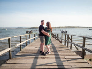 Couple on engagement photo session, holding each other on Lake Pier, Poole Harbour, Dorset