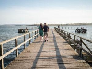 Couple on engagement photo session, walking along Lake Pier, Poole Harbour, Dorset