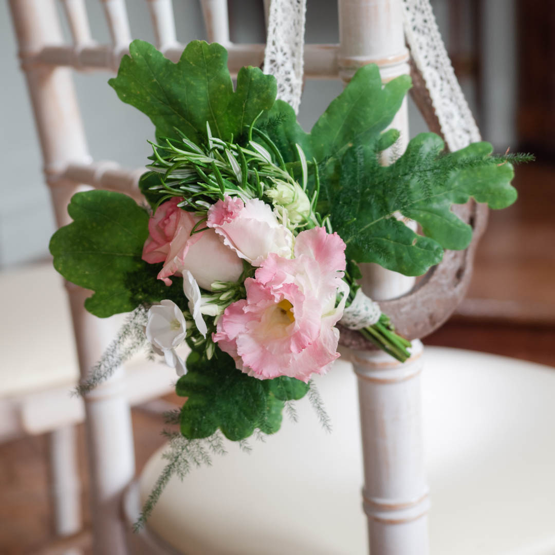 Wedding decoration featuring roses and oak leaves tied to a chair