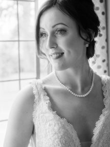 Monochrome image of bride by a window