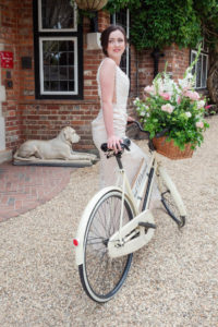 Bride on a bicycle with flowers in the front basket
