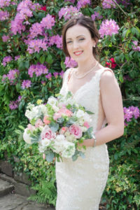 Bride holding bouquet of roses, standing in front of azaleas