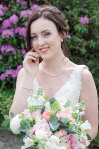 Bride holding bouquet of roses, with azaleas in the background