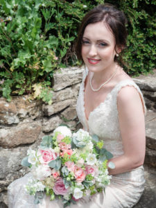 Bride sitting on stone steps, wih a bouquet of roses in her lap