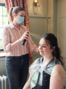 Stylist sprays a model's hair before a photo shoot