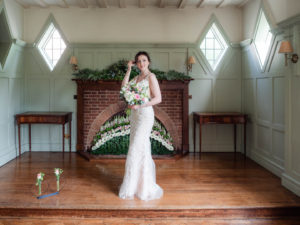 Bride poses with a bouquet  in front of the fireplace at the Montagu Arms Hotel, Beaulieu
