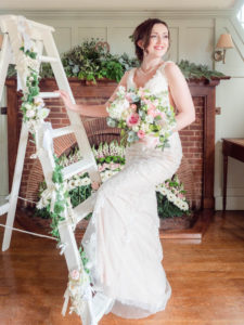 Bride poses on a decorated step ladder in The Montagu Arms Hotel, Beaulieu