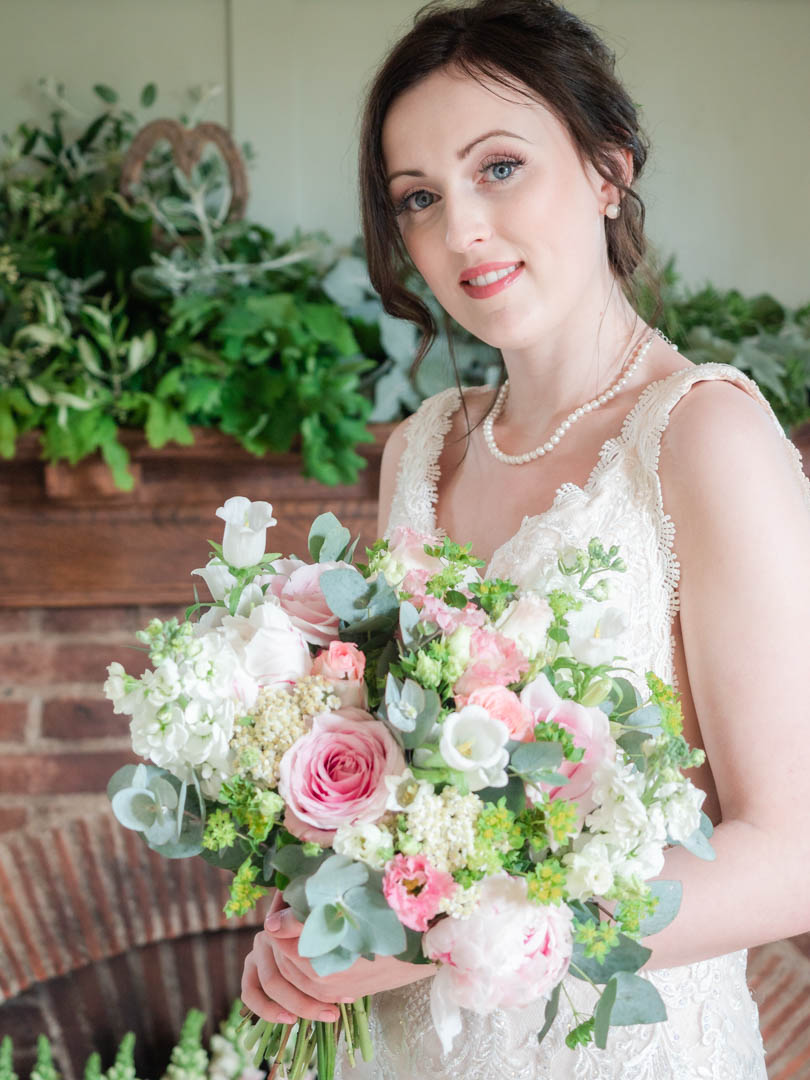 Bride holds a bouquet of roses in front of a hearth decorated with foliage