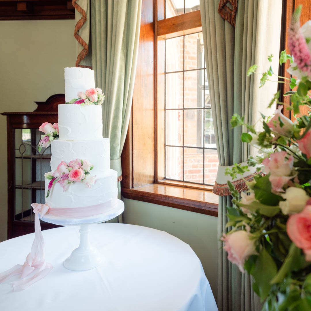 White wedding cake finished with pink roses by a window