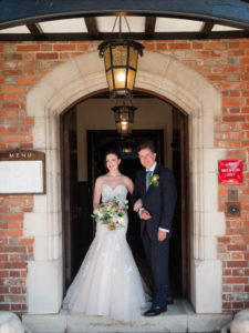 Bride and groom on the front steps of The Montagu Arms Hotel, Beaulieu