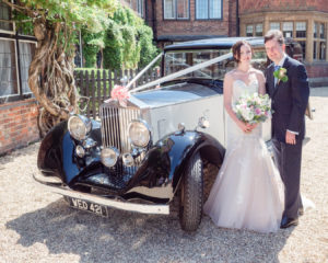 Bride and groom standing in front of a vintage Rolls Royce at The Montagu Arms Hotel