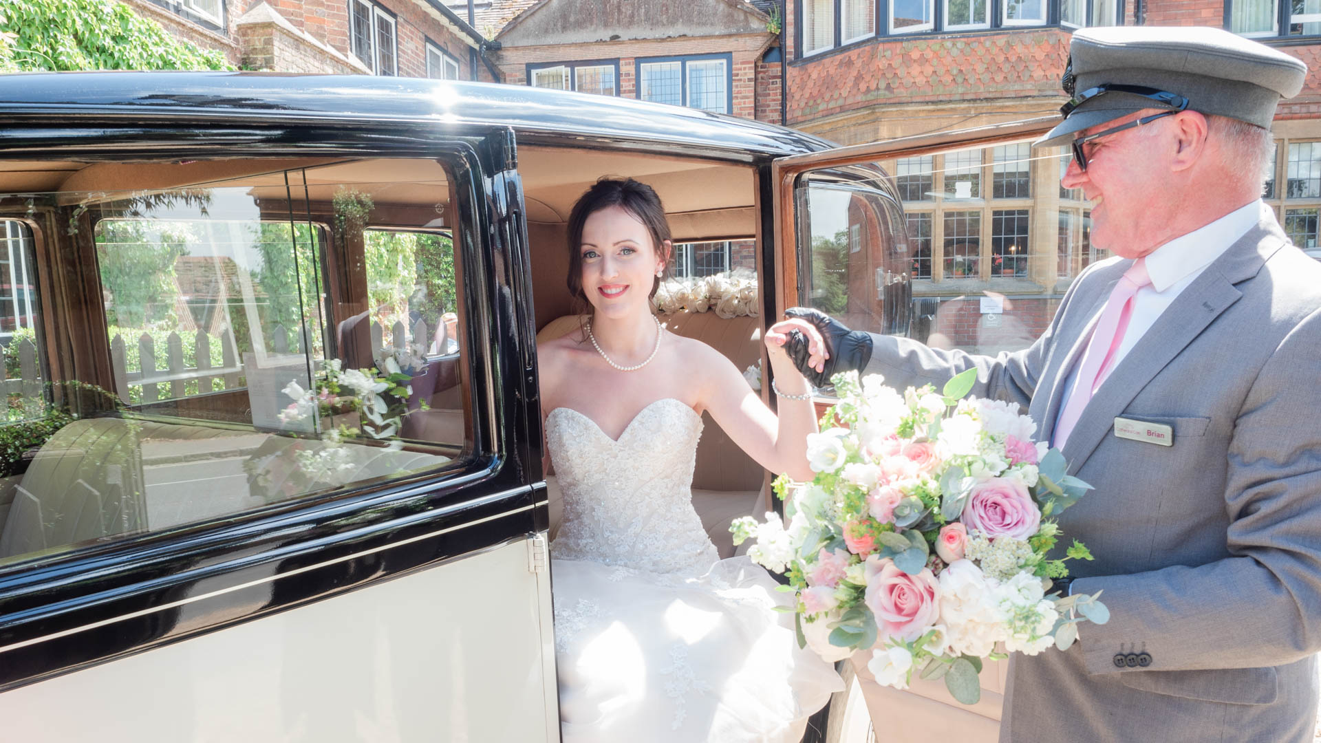 Chauffeur helps bride out of a vintage Rolls Royce at The Montagu Arms Hotel, Beaulieu