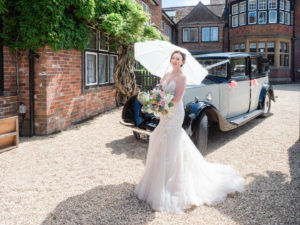 Bride holds a sun parasol and bouquet in front of a vintage Rolls Royce at The Montagu Arms Hotel, Beaulieu