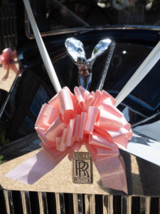Pink ribbon tied to The Spirit of Ecstasy on the bonnet of a vintage Rolls Royce