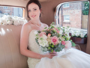 Bride holding a Rolls Royce seated in the back of a vintage Rolls Royce