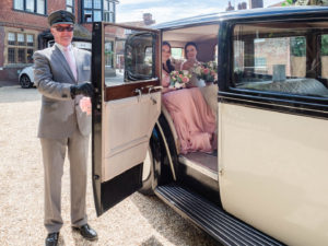 Chauffeur holds door of vintage Rolls Royce open for a bride and her bridesmaid