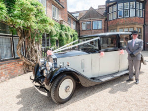 Chauffeur standing in front of a vintage Rolls Royce at The Montagu Arms Hotel, Beaulieu