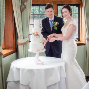 Bride and groom cutting the cake in The Paris Room in The Montagu Arms, Beaulieu