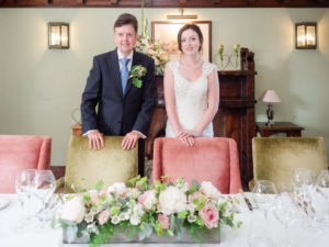 Bride and groom ready to sit for their wedding breakfast in the Paris Room at the Montagu Arms Hotel, Beaulieu